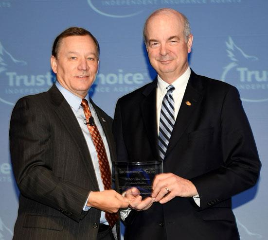 EMC President and CEO Bruce Kelley holding an award with Big I President Robert Rusbuldt.