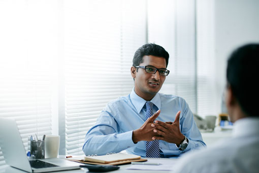 Man with glasses at desk gesturing to another person