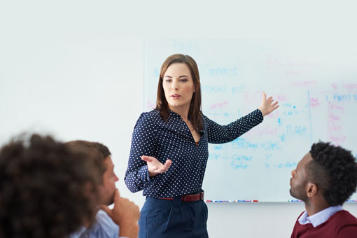 Woman pointing to whiteboard during a meeting