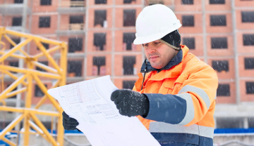 EMC contractor assessing blueprints at a construction site