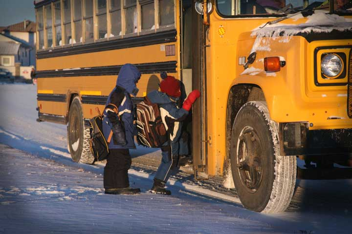 Bundled up children in the snow stepping onto the school bus