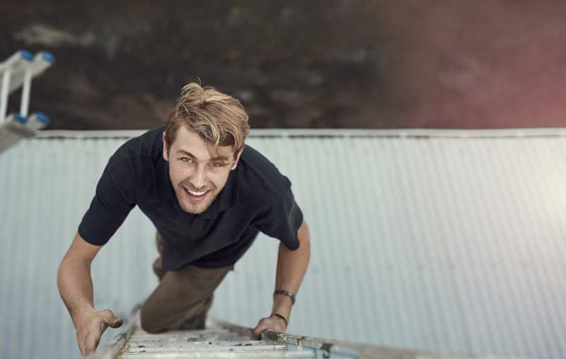 Smiling young man climbing a ladder