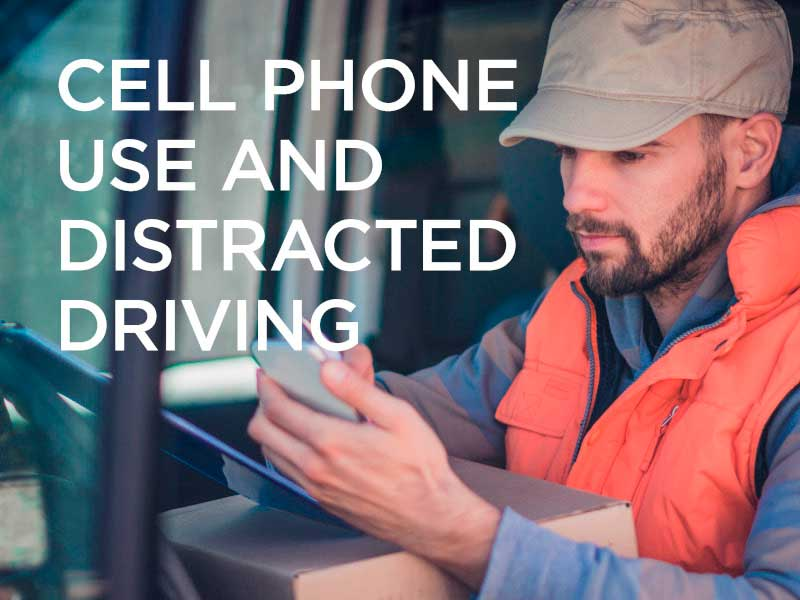 Man in orange vest and nude colored hat sitting in truck and looking at his phone.