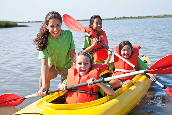 A camp counselor and three campers in a kayak on the water.