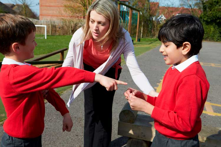 A teacher consuling two students who are having a disagreement