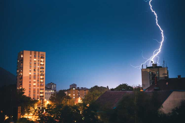 lightning striking a lightning pole on top of a building