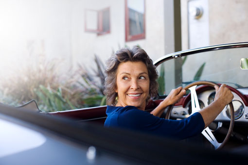 Photo of woman in a vintage convertible car
