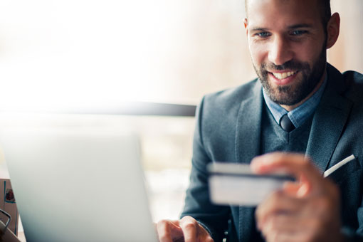 Photo of a man using his credit card online
