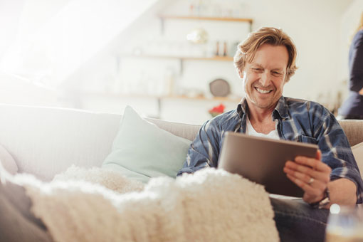 Photo of a man smiling while looking at a tablet